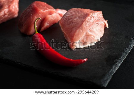 raw meat and chilli pepper on black slate background