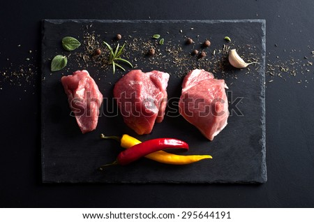 raw meat and spices on black slate background - stock photo