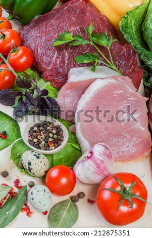 Raw meat and spices on rustic wooden board - stock photo