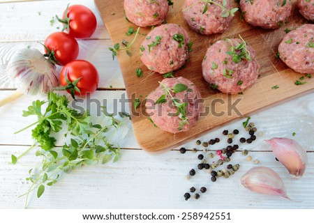 Raw meat balls with fresh herbs on wooden board - stock photo