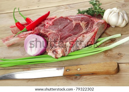 raw meat : boned fresh lamb ribs served with thyme , garlic and red chili pepper on wooden board