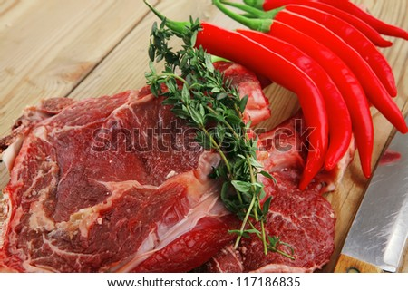 raw meat : boned fresh lamb ribs served with thyme , red chili pepper , and green onion on wooden board - stock photo