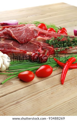 raw meat : boned fresh lamb ribs served with thyme , red chili pepper , cherry tomato , and green onion over wooden table - stock photo