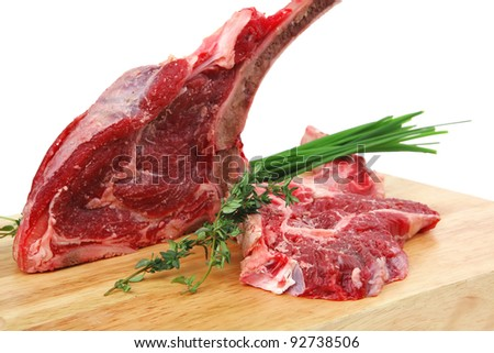 raw meat : boned fresh ribs served with thyme and green chives on wooden board isolated over white background - stock photo