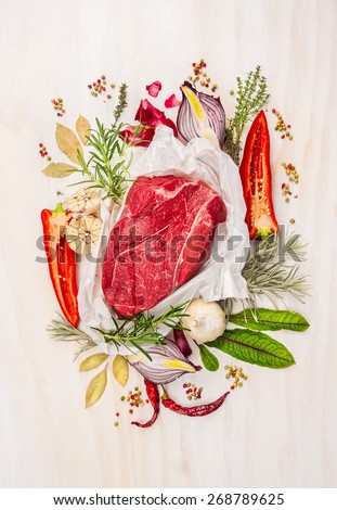 Raw meat, composing with herbs,spices and seasoning on white wooden background, ingredients for cooking, top view - stock photo