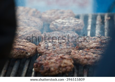 raw meat for a hamburger on the grill roasting on the street - stock photo