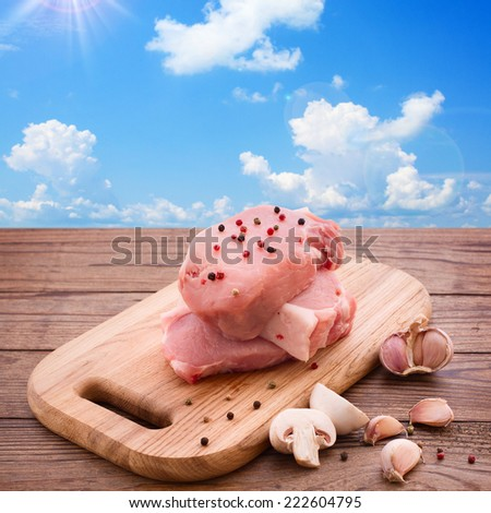 Raw meat for barbecue with fresh vegetables and mushroom wooden surface. Food, meat raw steak, beef steak bbq, spices for cooking meat. Background blue sky with clouds and sun - stock photo