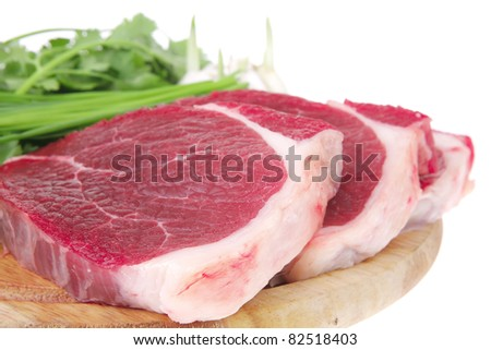 raw meat : fresh beef pork fillet pieces with garlic and green stuff on wood isolated over white background - stock photo