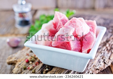 raw meat in bowl and on a table - stock photo