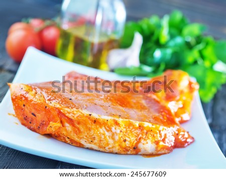 raw meat in marinad and on wooden board - stock photo
