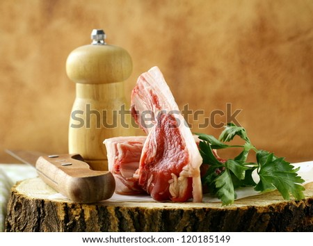 raw meat, lamb chops on a wooden cutting board - stock photo
