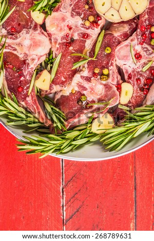 Raw meat lamb loin chops with rosemary and garlic in white frying pan, close up, top view, place for text - stock photo