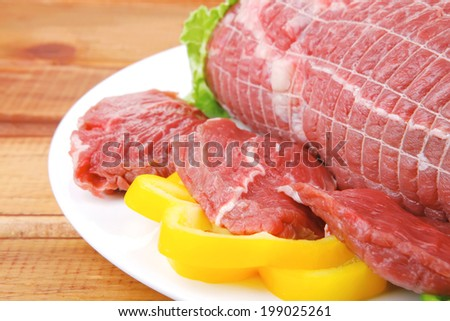 raw meat on plate over wooden table - stock photo