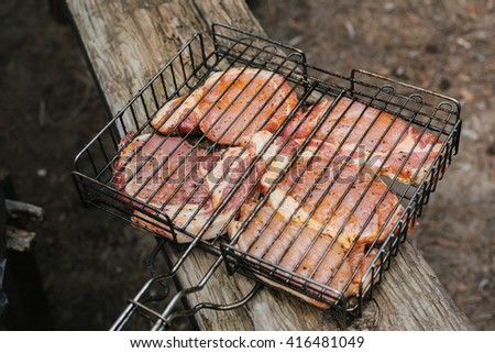 Raw meat on the grill. The concept of eating outdoors in the weekend. - stock photo