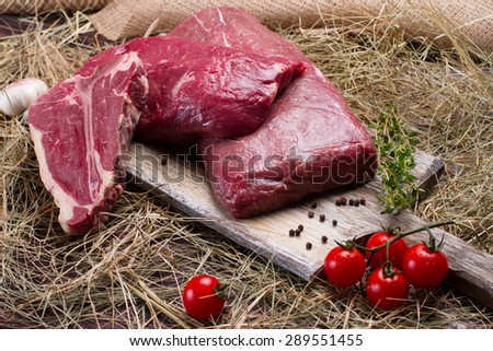 Raw meat on wooden cutting board with tomatoes. - stock photo