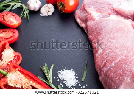 Raw meat pork with pepper, tomatoes, rosemary and garlic on a dark table. Ingredients for cooking. Selective focus - stock photo