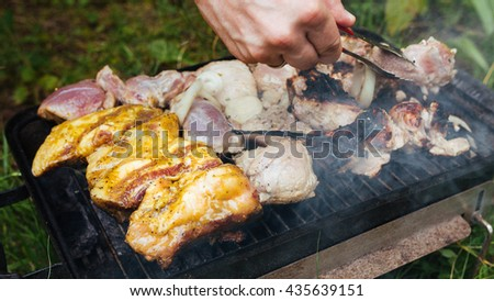 Raw meat prepared on the grill and grill. Cooking barbecue on grill flame. Food meat preparing on nature picnic outdoors. Meat on bbq barbecue grill. Marinated chicken legs on barbecue grill. - stock photo