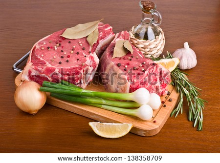 Raw meat selection on wooden cutting board with vegetables - stock photo