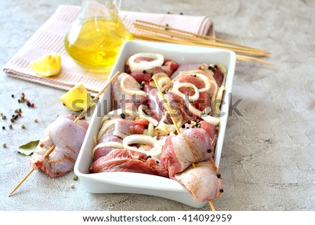 Raw meat skewers of turkey in a dish on the table with spices - stock photo