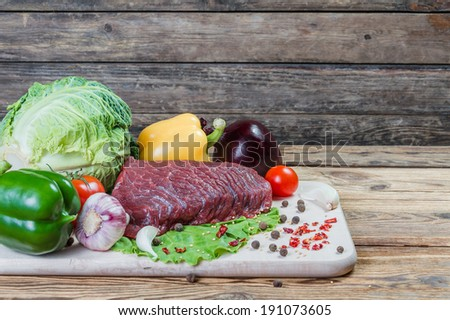 Raw meat, spices and vegetables on rustic wooden board - stock photo