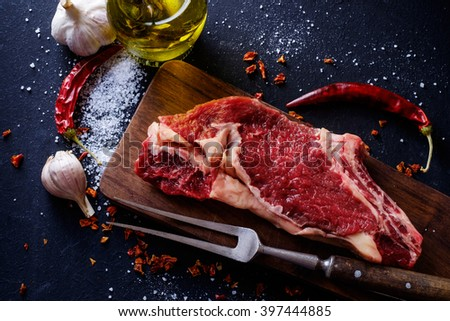 Raw meat steak entrecote on the cutting board with spice on the dark table.  - stock photo