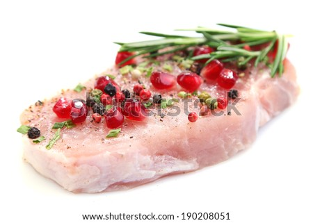 Raw meat steak with herbs, spices and pomegranate seeds, isolated on white