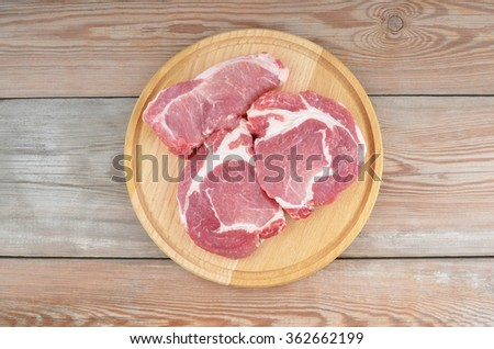 Raw meat steaks on board over wooden background, DOF - stock photo