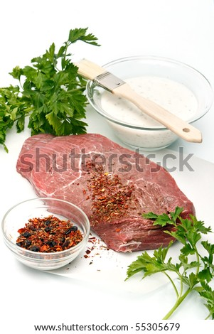 Raw meat steaks with herbs and sauce on white background - stock photo