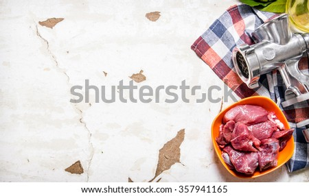 Raw meat with a hand grinder on the fabric. On rustic background. Free space for text . Top view - stock photo