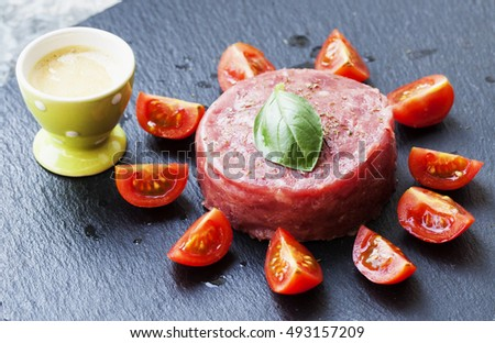 Raw meat with tomatoes and sauce, horizontal image