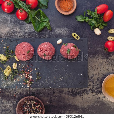 Raw meatballs and meatball ingredients.  Minced meat mixture for meatballs and ingredients on dark background. Top view, vintage toned image, blank space  - stock photo
