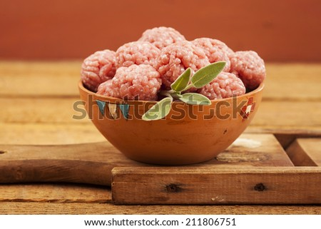 Raw meatballs in bowl with ingredients on wooden background - stock photo