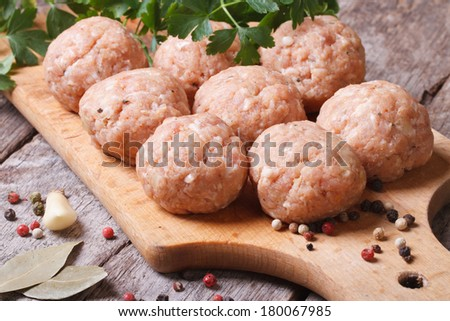 raw meatballs on a chopping board and ingredients. horizontal. close-up  - stock photo