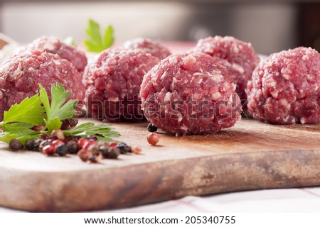 Raw meatballs on a chopping board with ingredients - stock photo