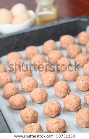 Raw meatballs on baking sheet, ready for roasting. Shallow DOF
