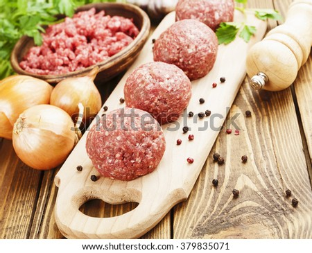 Raw meatballs on the wooden cutting board - stock photo