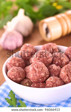 Raw meatballs with garlic in a white bowl (Selective Focus, Focus on the meatballs in the front)