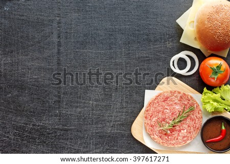 Raw minced beef (patty) with herbs, sesame bun, cheese, tomato, lettuce, onion, hot BBQ sauce, chili. Homemade hamburger ingredients. Black background. Space for text. - stock photo