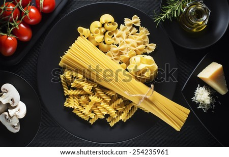Raw mixed pasta on black background overhead shoot - stock photo