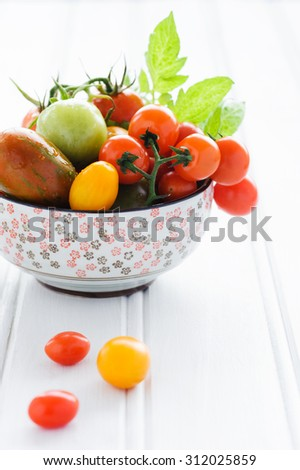 Raw mixed tomatoes in an ornate bowl, cherry, roma, green, yellow, vine ripened with fresh green leaves  - stock photo