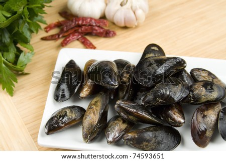 Raw mussels with garlic, chilli peppers and parsle - stock photo