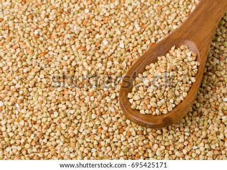 Raw, natural, uncooked buckwheat seed kernels in wooden spoon on buckwheat seed background