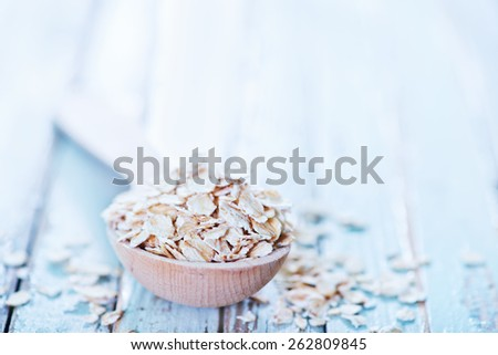 raw oat flakes in spoon and on a table - stock photo