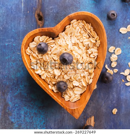 Raw oat flakes with fresh blueberry in heart shaped wooden bowl on blue rustic background. Square image. Selective focus