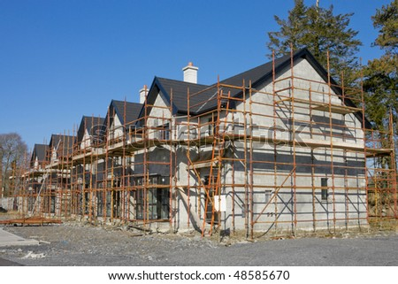 raw of houses with scaffolds in construction site - stock photo