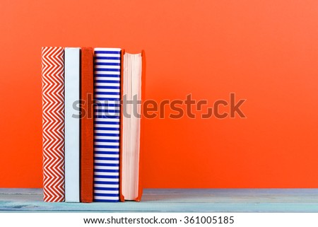 Raw of old hardback books, diary, on wooden deck table and red background. Books stacking. Back to school. Copy Space. Education background. - stock photo
