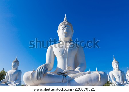 raw of white buddha status on blue sky background in thailand - stock photo