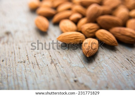 Raw Organic Almonds on Blue Wooden Surface - stock photo