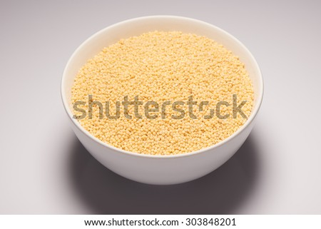 Raw organic millet croup in white ceramic bowl on white background - stock photo