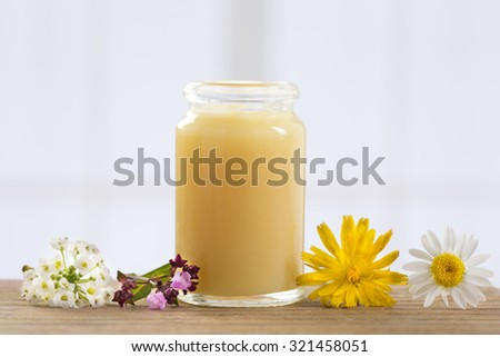 raw organic royal jelly in a small bottle with flowers - stock photo